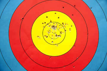 A standard archery target with arrow holes mostly in the 10-9 point section.