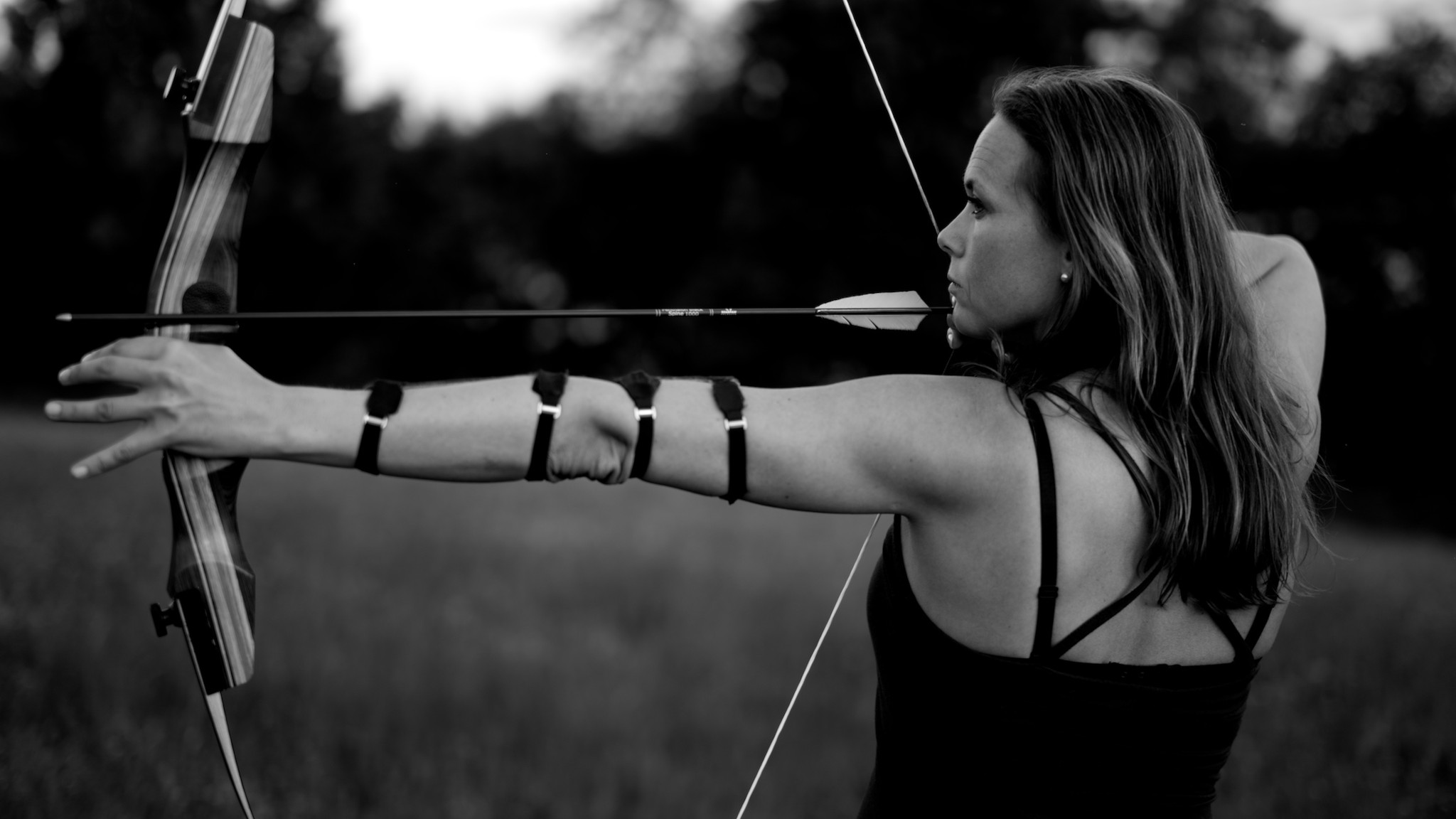 A black and white photo of a woman with a recurve bow nocked at full draw.