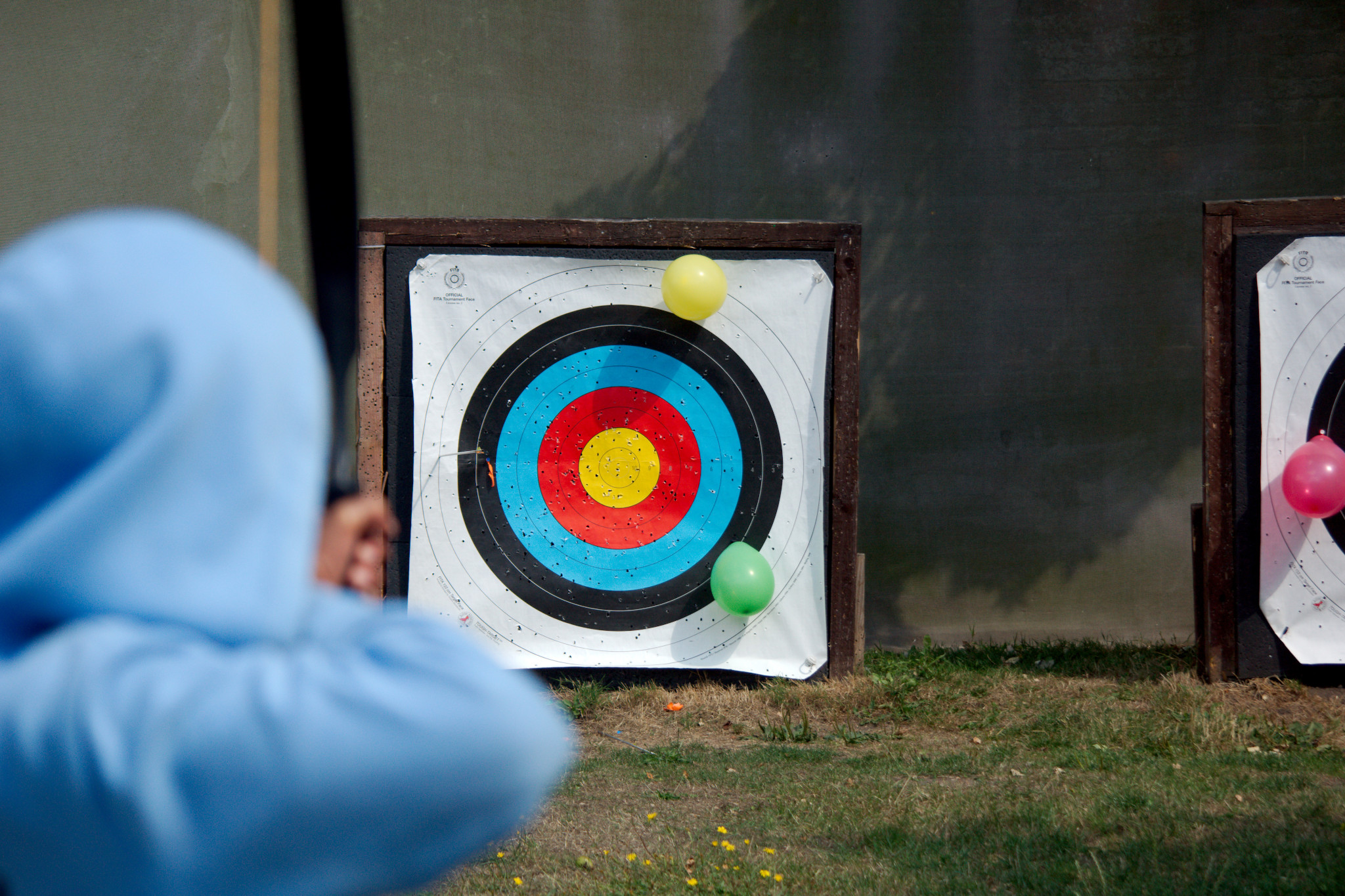 A youth in a blue hoodie from behind, aiming an arrow at a target hung with colourful balloons.