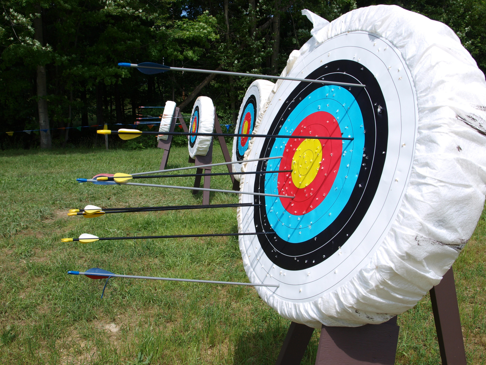 A row of 4 outdoor target butts filled with arrows, viewed from the side.